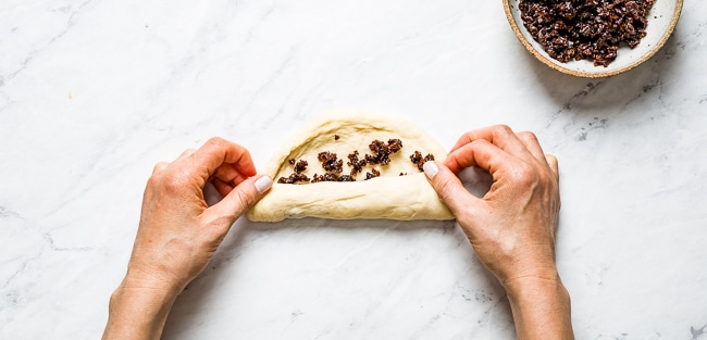 person pinching dough with raisins