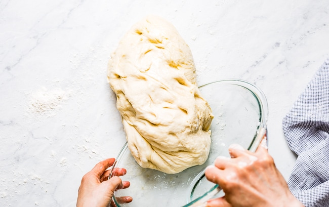 A woman is transferring Challah dough onto a marble surface