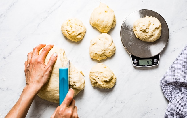 A woman is cutting the dough to make strands