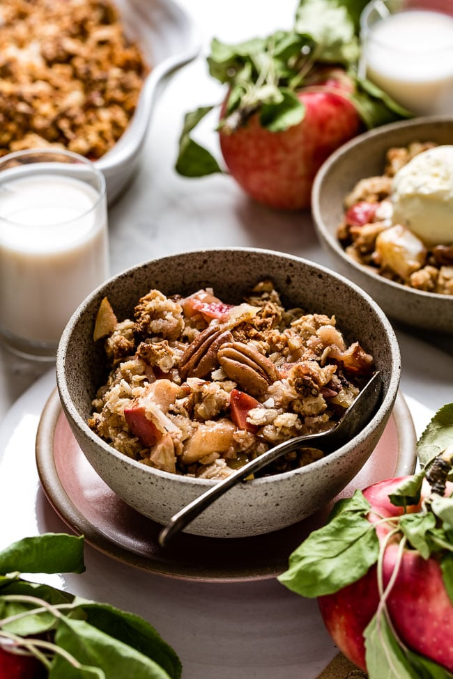 Vegan Apple Crisp placed in a bowl with milk on the side.