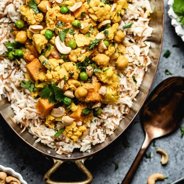 Cauliflower Curry with coconut milk and sweet potatoes placed in a copper pot garnished with cilantro and cashews from the top view