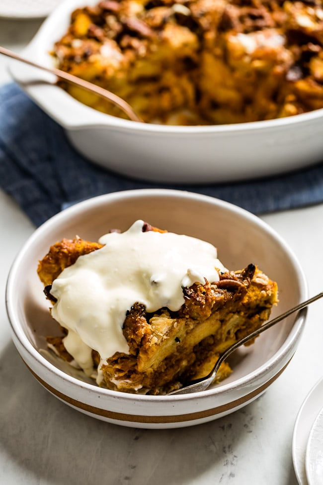 Pumpkin Bread Bread Pudding topped off with creme fraiche in a bowl with a spoon