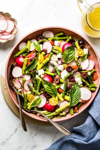 Asparagus Salad recipe served in a bowl with lemon vinaigrette on the side from top view