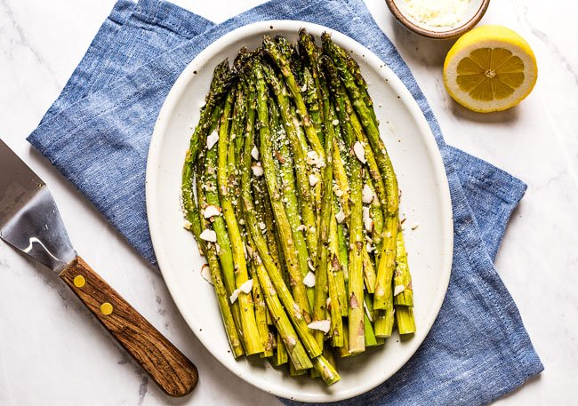 Oven Baked Asparagus with Parmesan in a plate with lemon on the side.