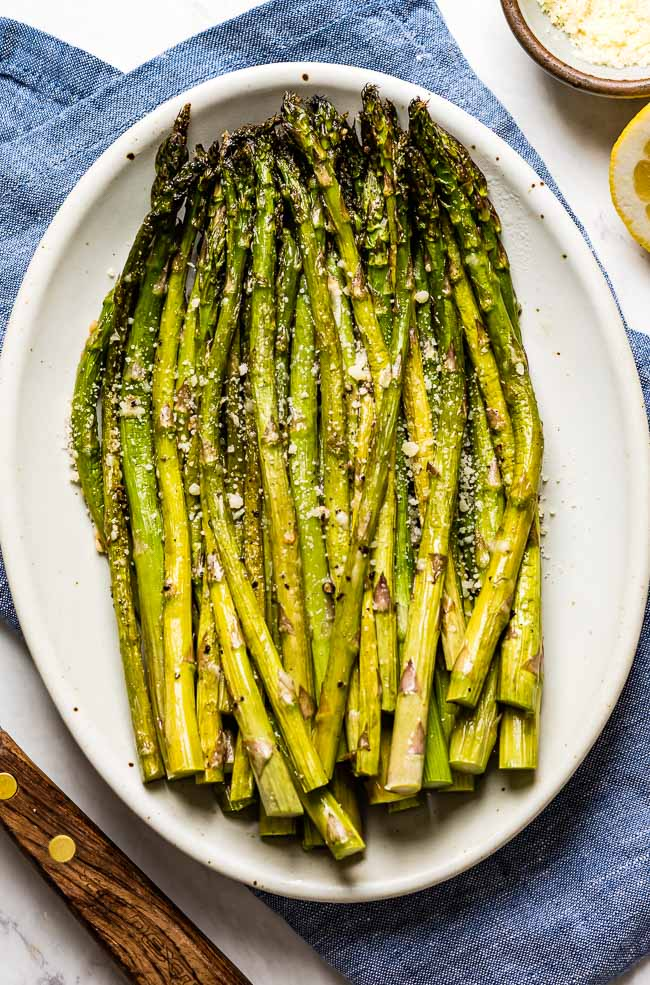 Freshly cooked asparagus in the oven on an oval plate