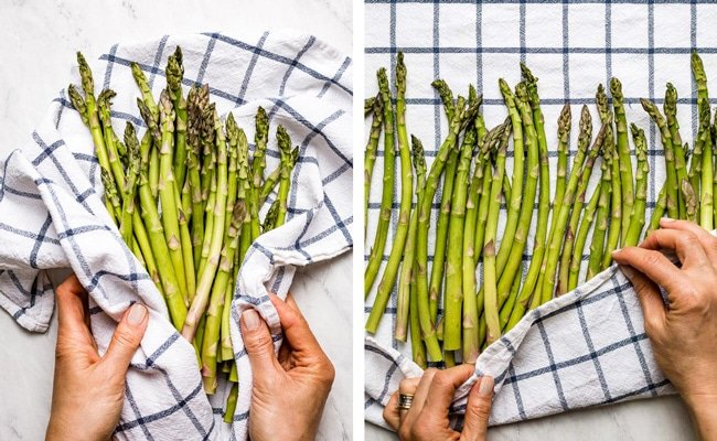 Person drying asparagus after washing it