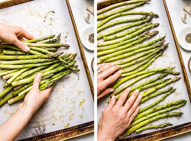 Person tossing asparagus to make sure it is fully coated and in one single layer on sheet pan