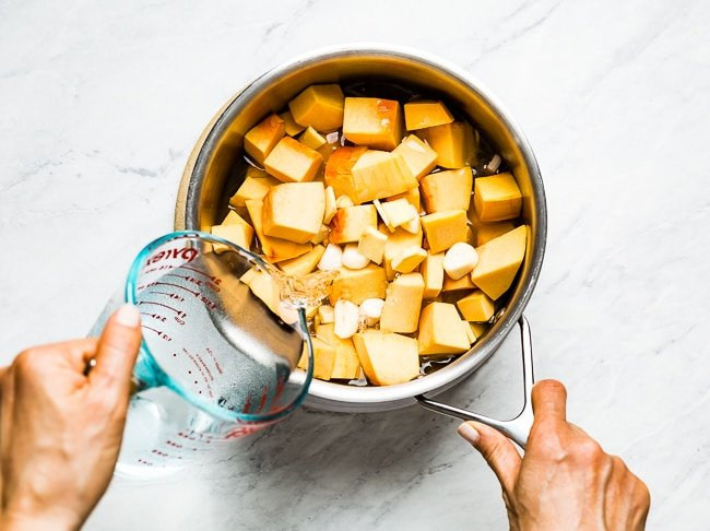 Person pouring liquid in soup pan