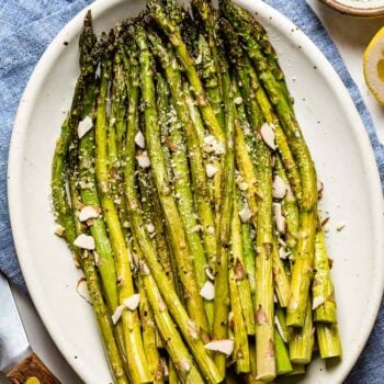 Baked Asparagus recipe placed on a plate and garnished with parmesan