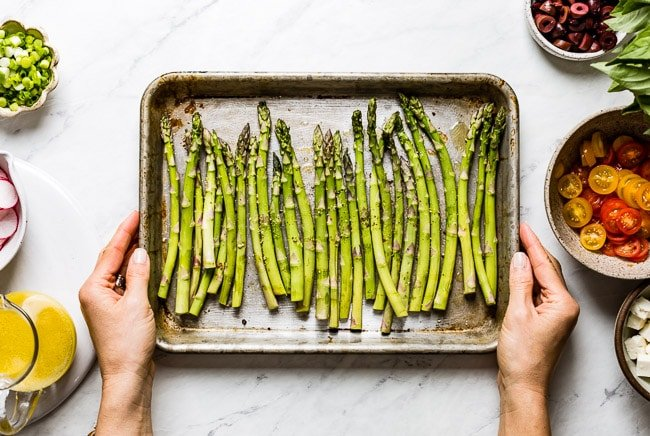 Person cooking asparagus for salad in a baking sheet