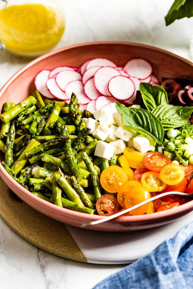 Cold asparagus salad recipe placed in a bowl with lemon dressing on the side