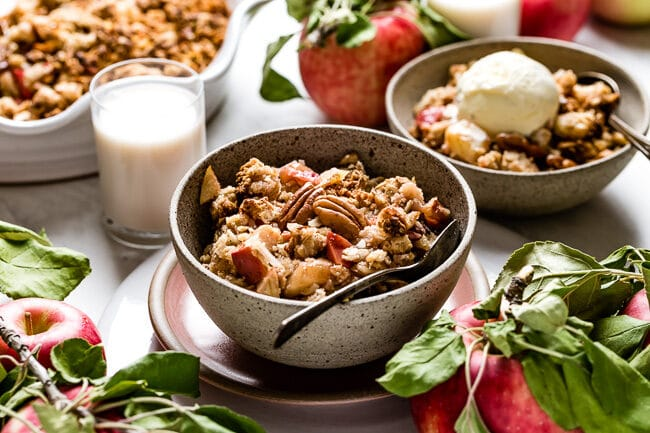 Vegan Apple Crisp in a bowl with a cup of milk on the side