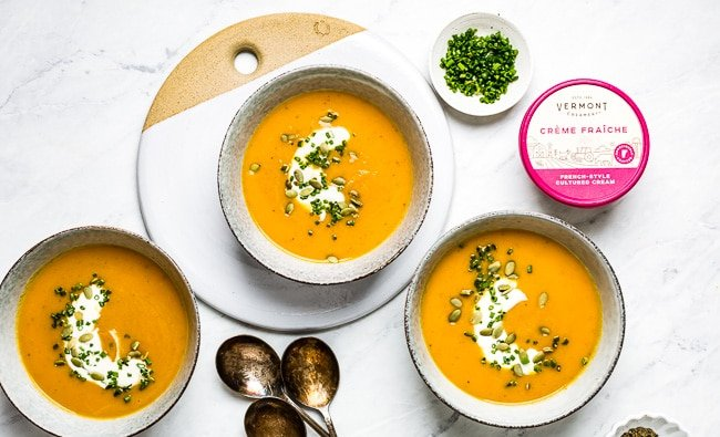 Three bowls of carrot soup with garnishes on top and on the side