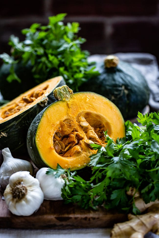 Japanese Kabocha squash is cut in half with garlic and herbs on the side