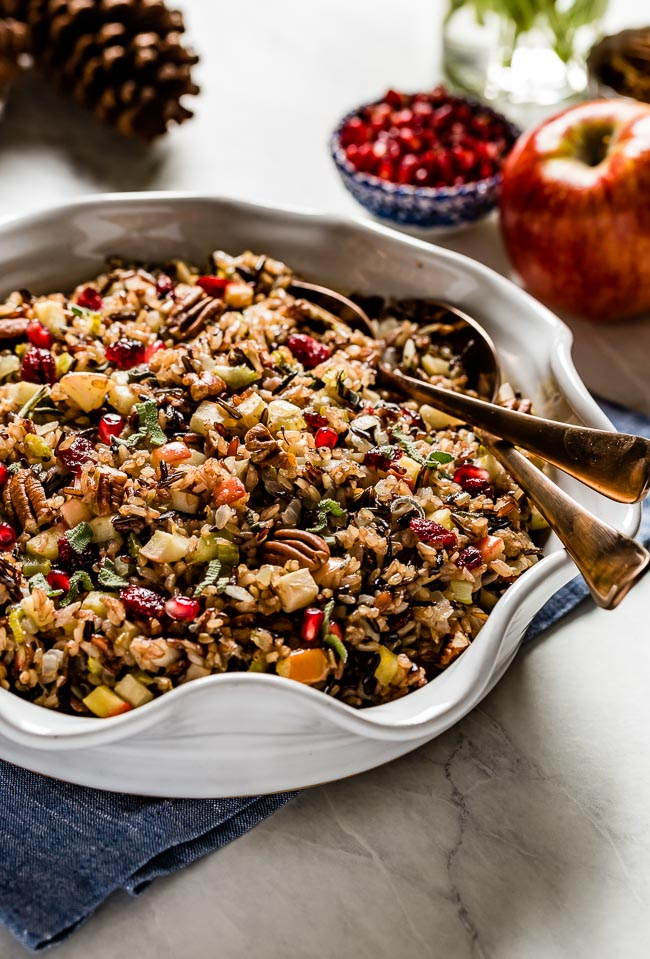 Wild rice dressing in a casserole dish with two spoons in the bowl for serving