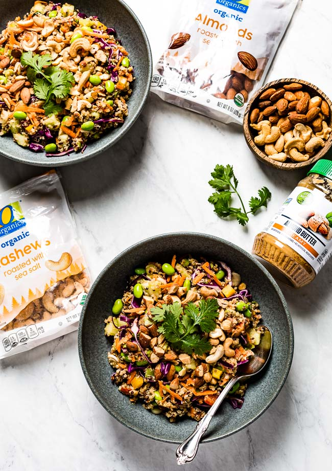 Vegan quinoa salad garnished with nuts and cilantro served in bowls from the top view