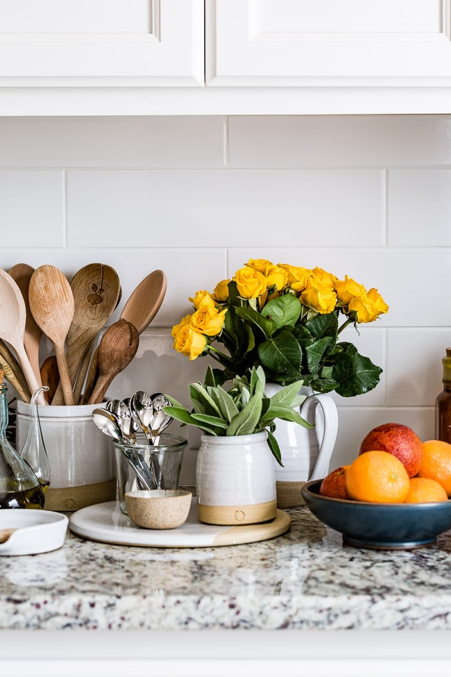 A kitchen counter with white pottery and yellow roses