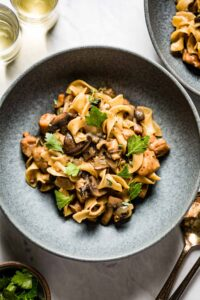 Chicken Stroganoff in a bowl garnished with parsley and thyme