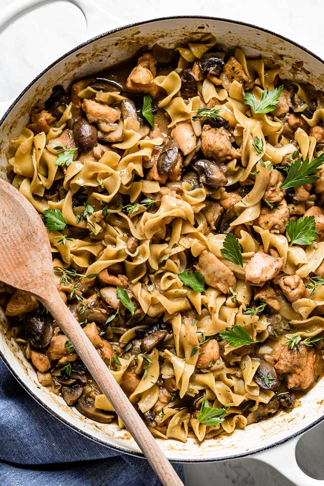Chicken stroganoff with mushrooms and egg noodles in a large pan