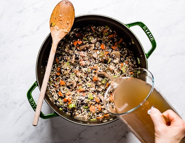 Person pouring stock into a large pot with rice and veggies