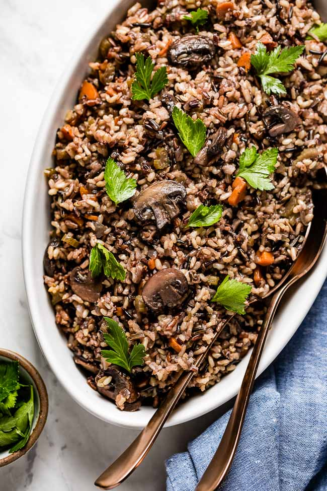 Wild Rice Mushroom Pilaf in an oval bowl with two spoons on the side.