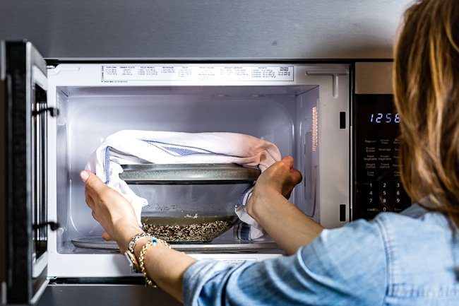 Person removing cooked quinoa from the microwave