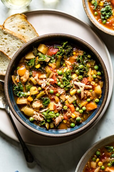 Chicken vegetable soup in a bowl with a spoon on the side