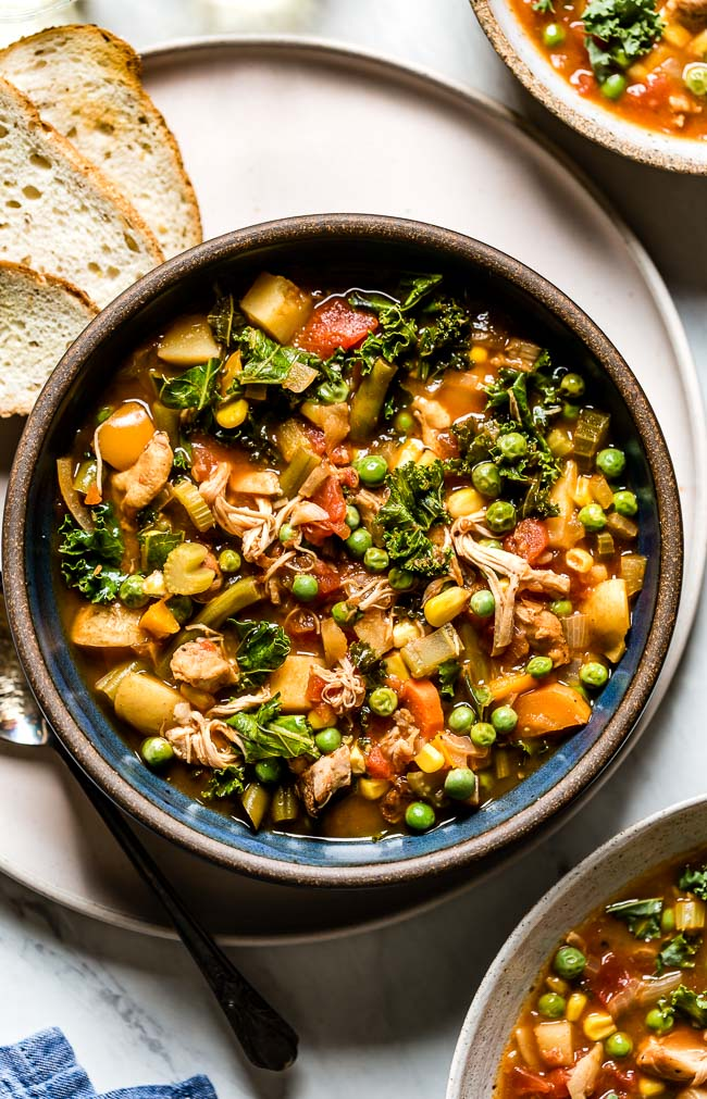Chicken and Vegetable Soup recipe placed in a bowl with bread on the side from the top view
