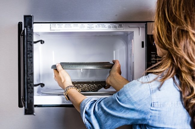 Person placing the bowl in the microwave