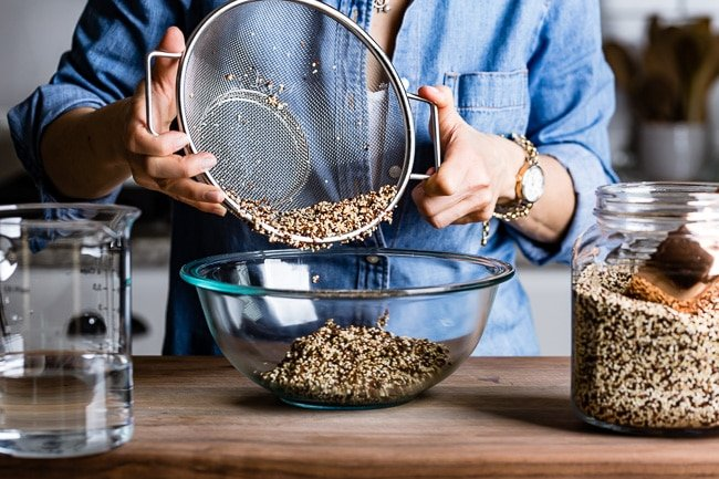 Person placing rinsed quinoa into a bowl from the front view.