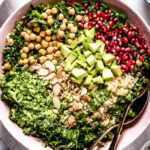 Kale quinoa salad placed in a bowl with two spoons on the side