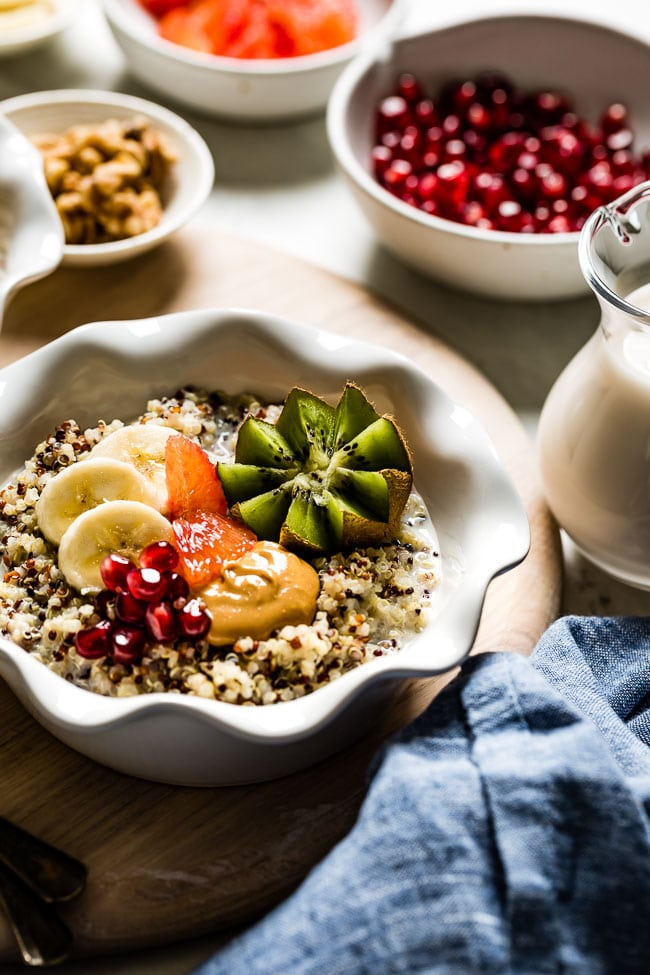A bowl of cooked quinoa topped off with fruit from the front view