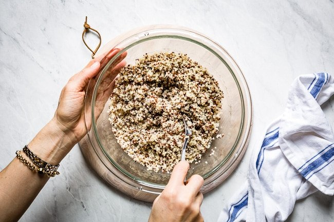 Person fluffing microwave quinoa with a fork