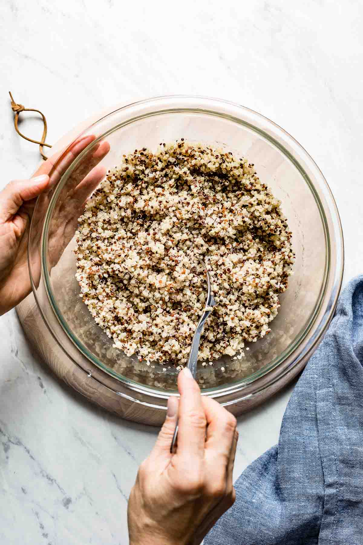 Microwave quinoa placed in a bowl and being fluffed by a woman