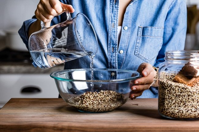 person pouring water into a cup with quinoa