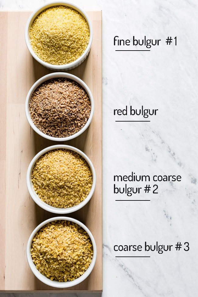 Various sizes of bulgur wheat placed in bowls with their names written next to them.