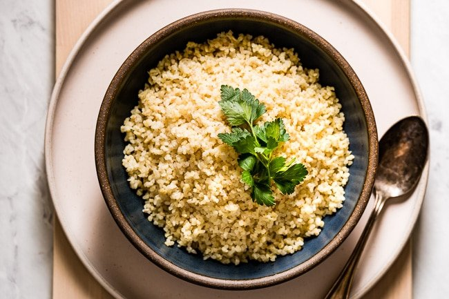 A bowl of cooked bulgur garnished with parsley