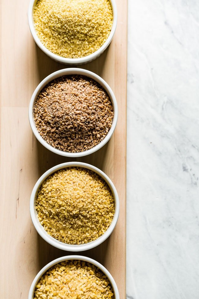 Different sizes of bulgar wheat placed in four bowls from the top view