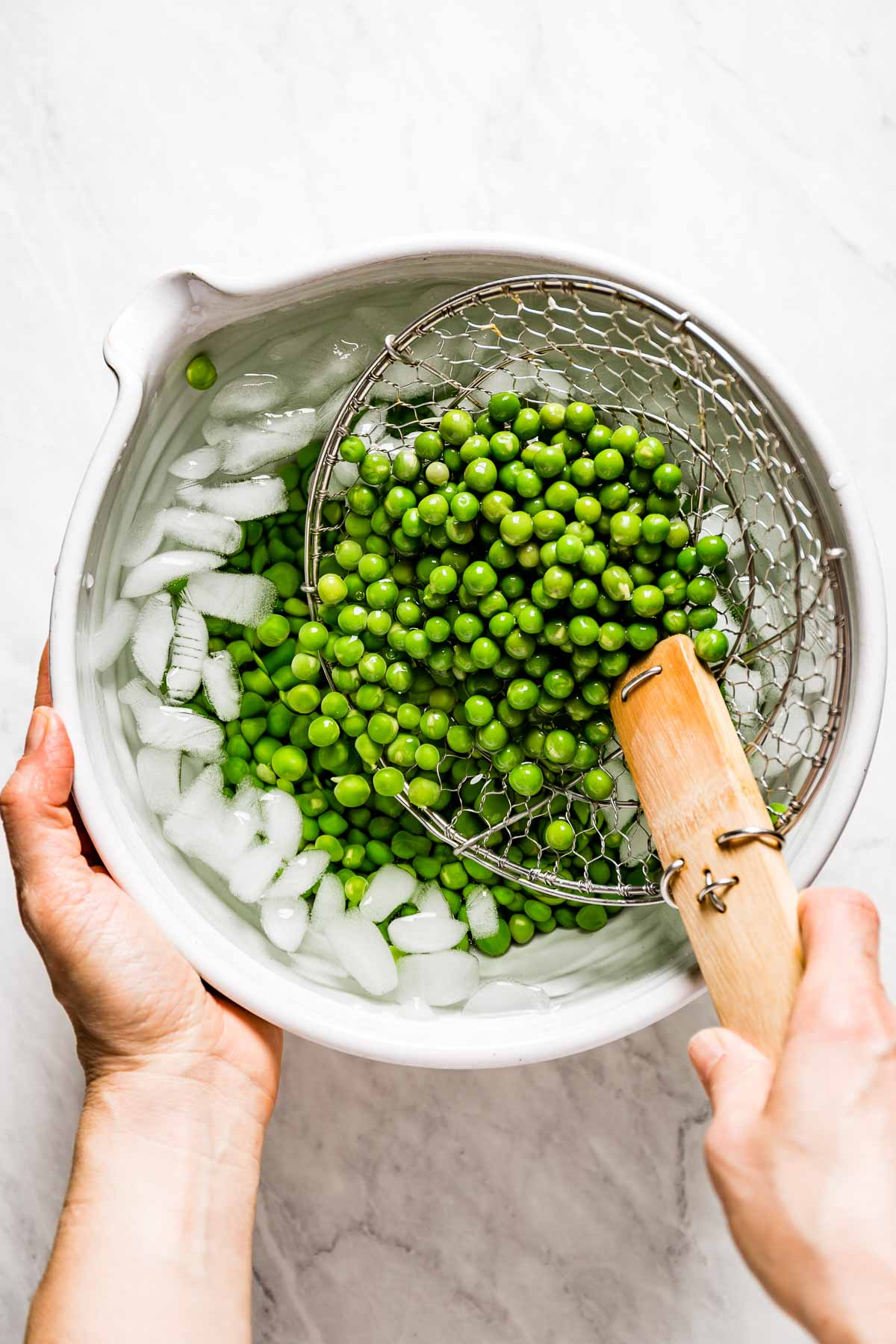 Person placing blanched peas into bowl with ice water