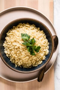 A bowl of cooked bulgur wheat in a bowl with a spoon on the side