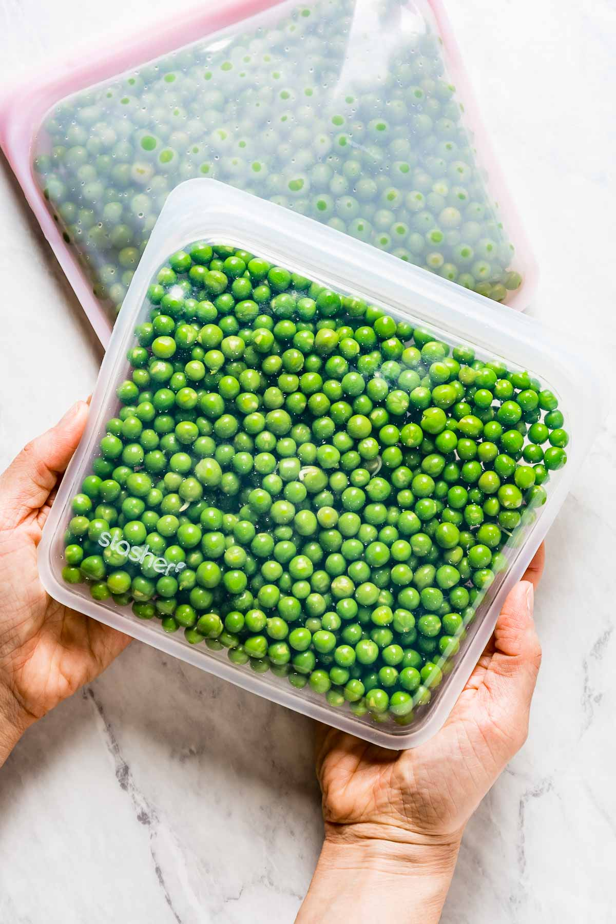 Person holding a freezer bag filled with blanched sweet peas