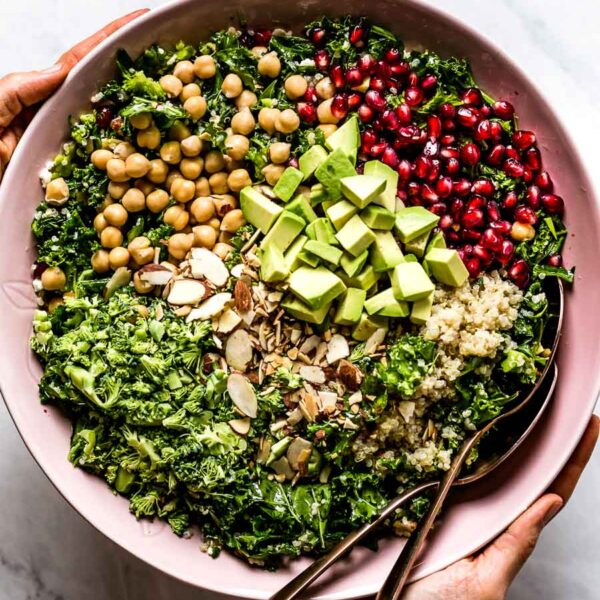 Kale Quinoa Salad is being served by a person on a marble background