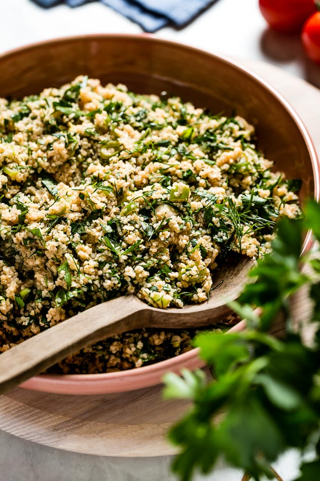 A bowl of Middle Eastern tabbouleh salad recipe in a bowl with a wooden spoon on the side.