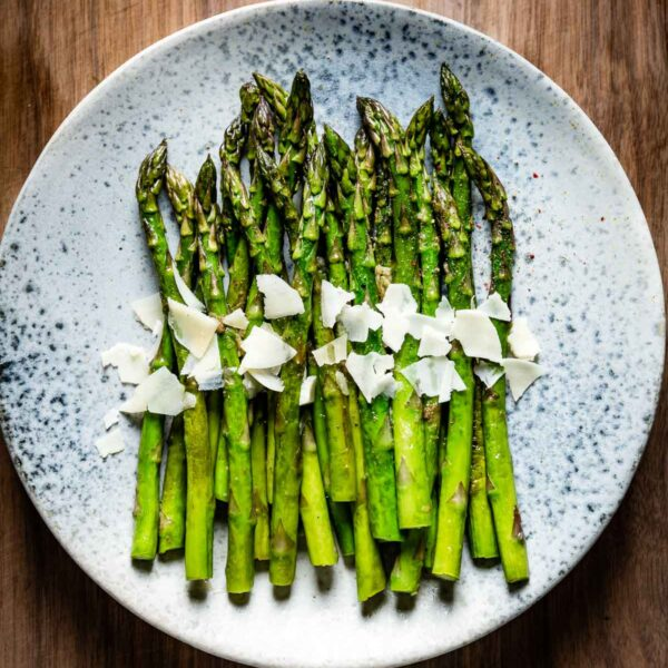Sauteed asparagus topped off with parmesan cheese in a blue plate