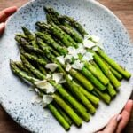Sauteed Asparagus Recipe topped off with parmesan cheese on a plate