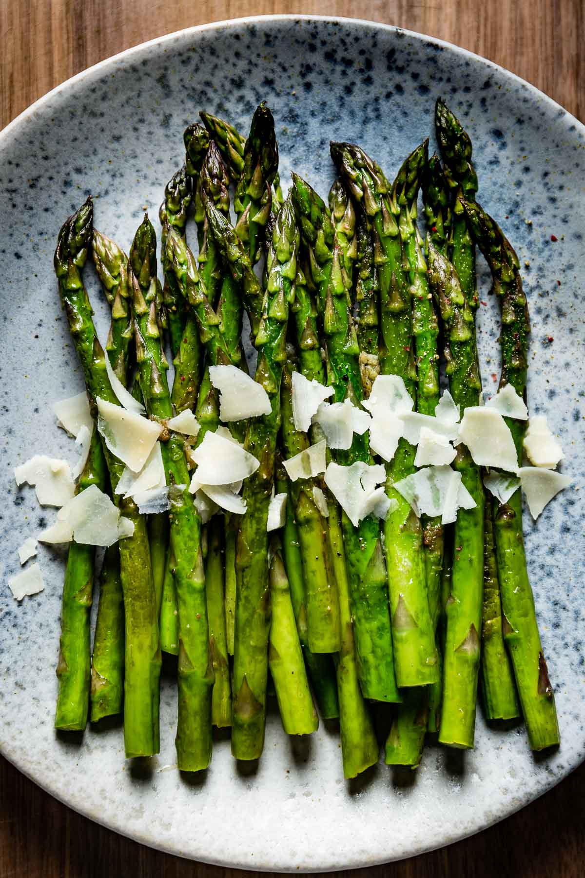 Sauteed Asparagus topped off with parmesan cheese on a plate