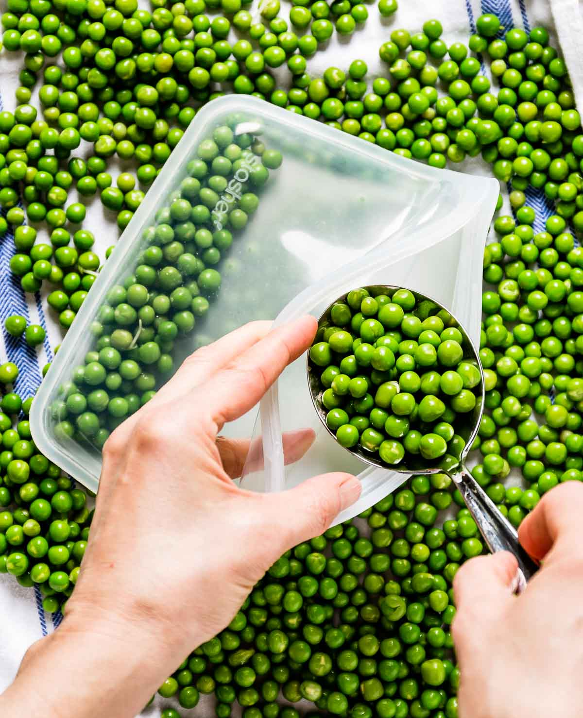 Person storing peas in a freezer bag with a spoon