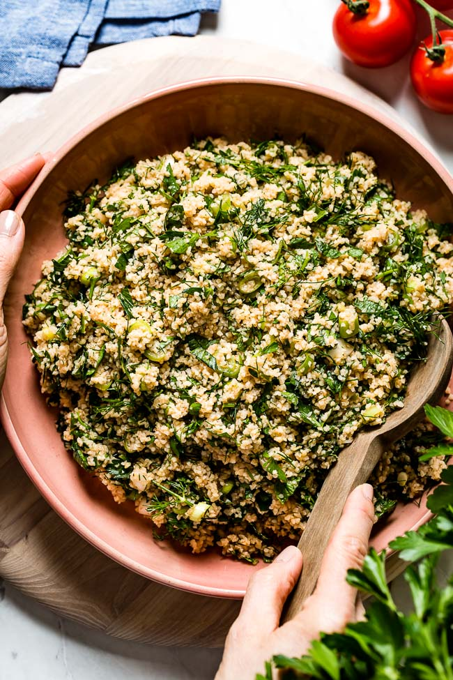 Tabbouleh salad served in a bowl by a person from top view