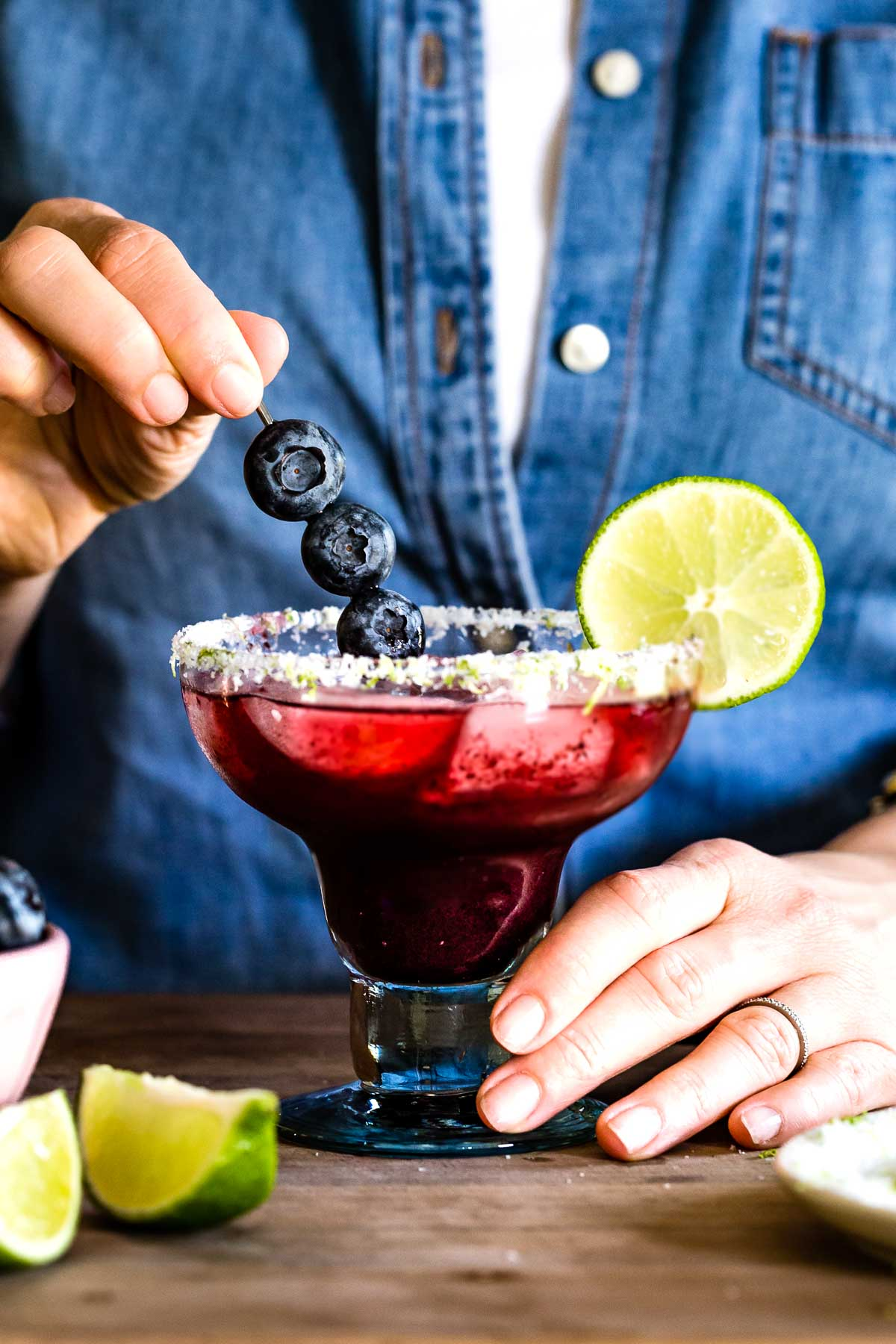 Person garnishing blueberry puree cocktail with blueberries