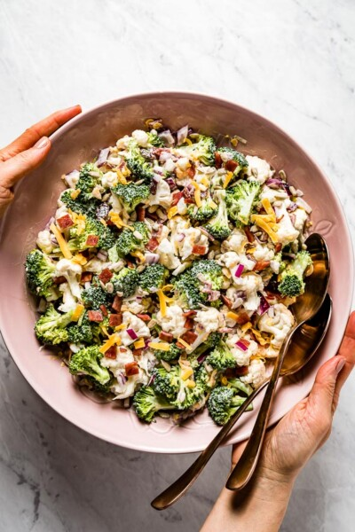 Broccoli Cauliflower Salad recipe served in a bowl by a person